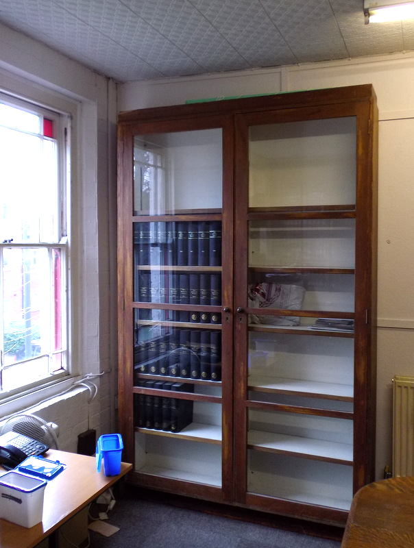 The glass fronted wooden bookcases.