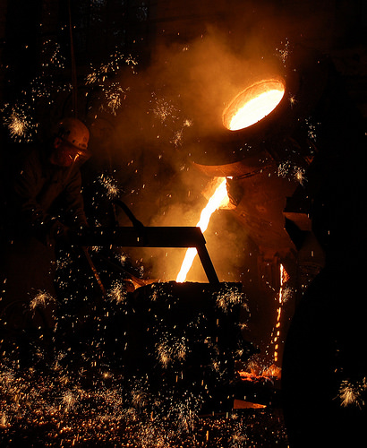 Preparing to cast a bell - metal pours from the furnace into a crucible.