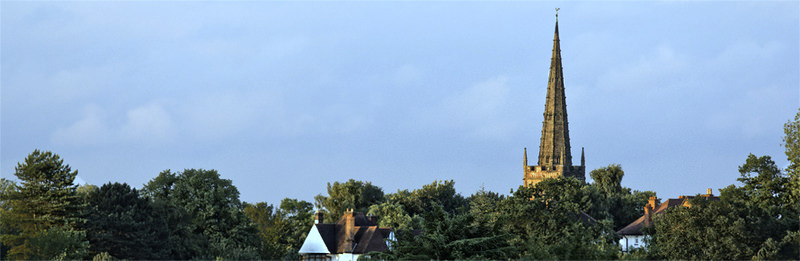 The mediaeval spire of St. Nicholas, Kings Norton rises above the tree line.