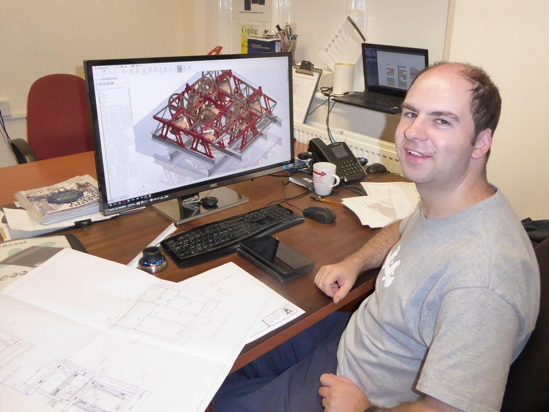Tom Onyon sitting at his computer with a new bell frame design.