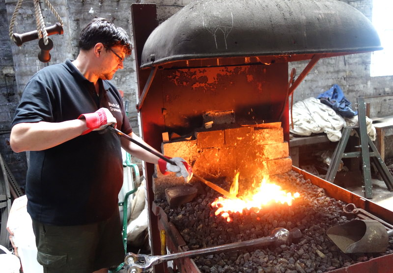 Our forge is not used as much nowadays, but here Carl prepares to anneal a repaired clapper.