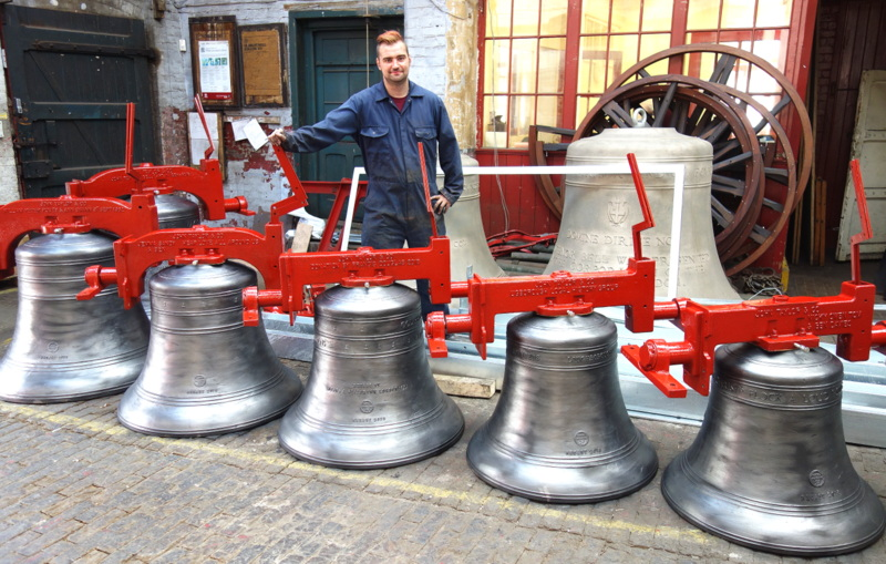 Ugborough's new bells are ready for dispatch. Will applies the final polish before they leave.