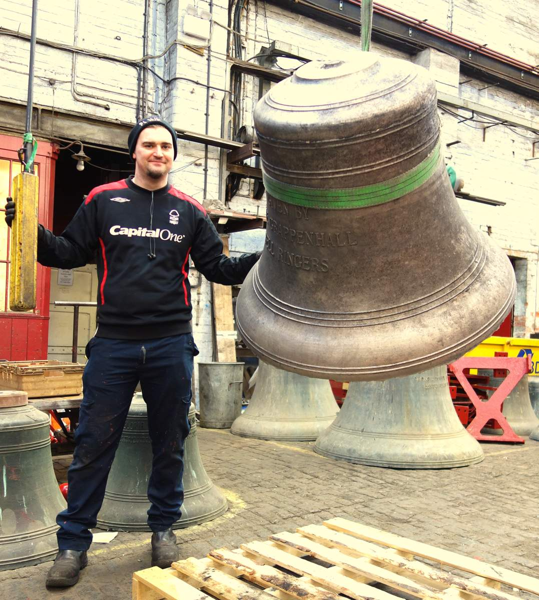 Will moves the newly cast tenor bell into the works for fettling.